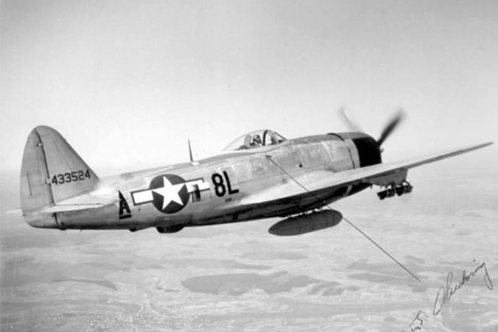 "A P-47 in flight with belly tank attached and fragmentation bombs on the wings (this aircraft was flown by Edwin J. ""Chick"" Chickering and the photo is signed by him)"