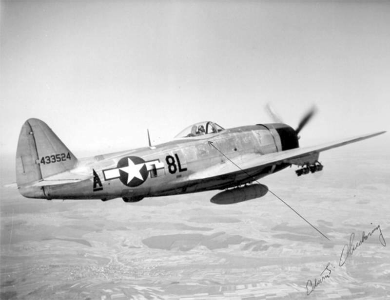 """A P-47 in flight with belly tank attached and fragmentation bombs on the wings (this aircraft was flown by Edwin J. """"Chick"""" Chickering and the photo is signed by him)"""